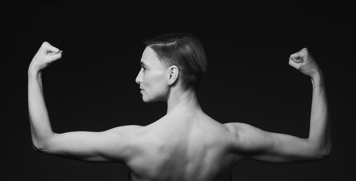 Kobieta napinająca bicepsy stojąca tyłem