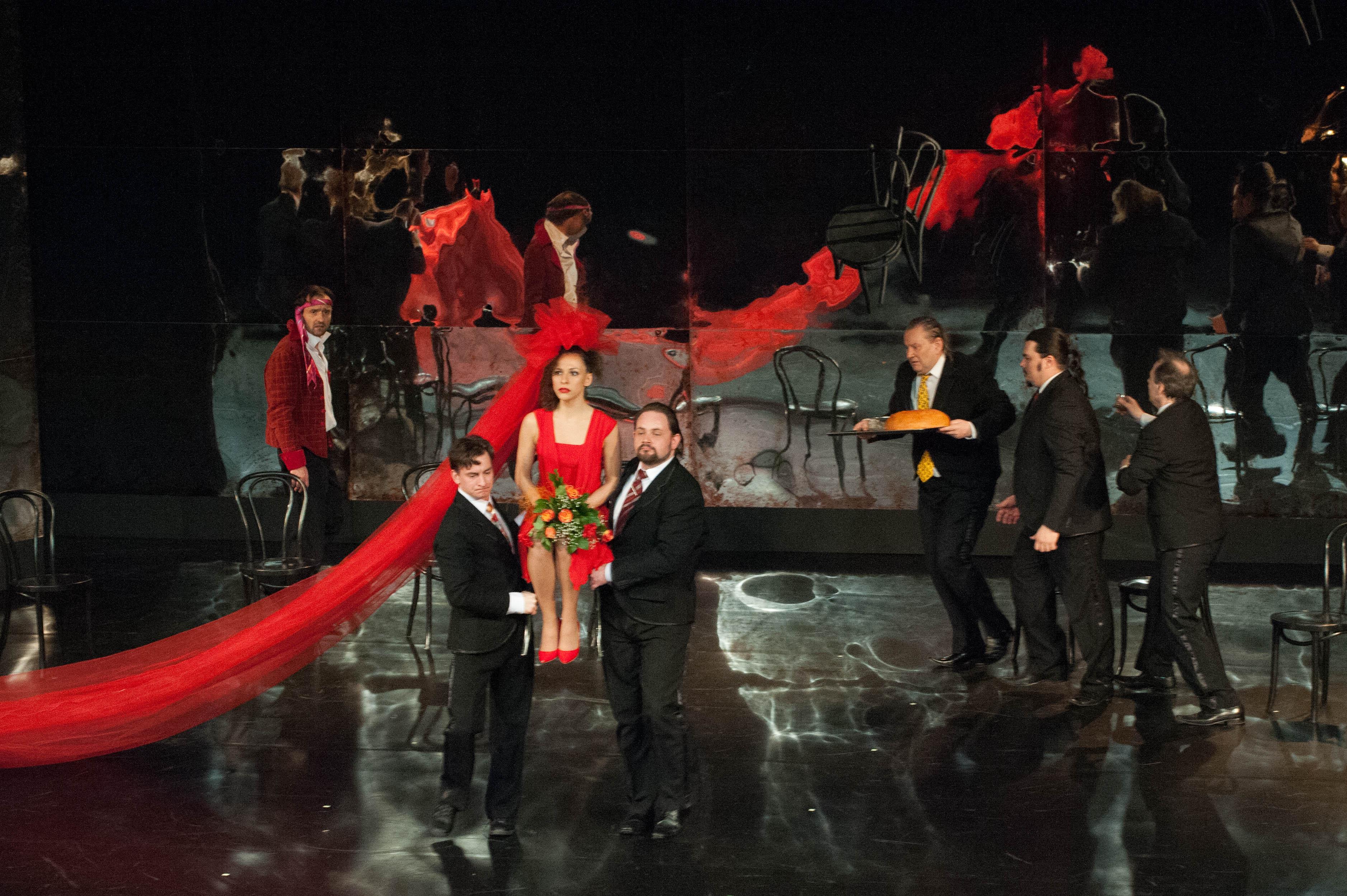 Aktorzy w garniturach niosą siedzącą na krześle aktorkę w czerwonej sukni